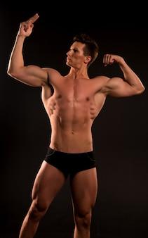 Gespierde man. gespierde man met buikspieren. gespierde man bodybuilder punt op zijn spier. biceps en triceps van gespierde man atleet. zijn lichaam in goede conditie te houden.