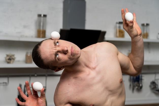 Gespierde man in de keuken eieren in evenwicht te brengen.