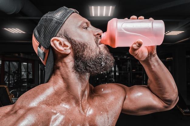 Gespierde man in de sportschool drinken uit een shaker. fitness en bodybuilding concept.