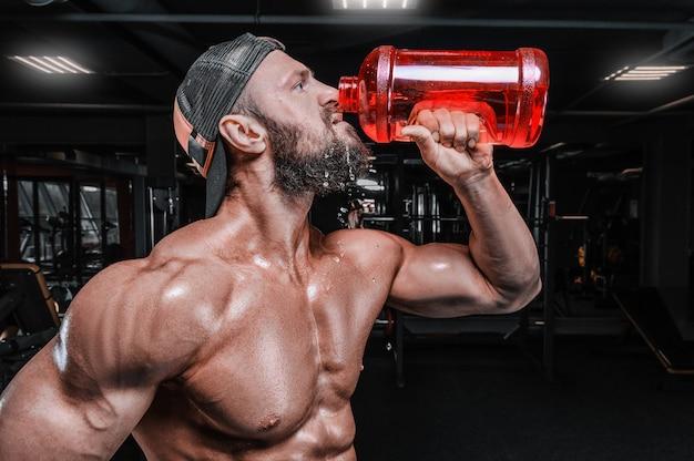 Gespierde man in de sportschool drinkt uit een enorme fles. fitness en bodybuilding concept.