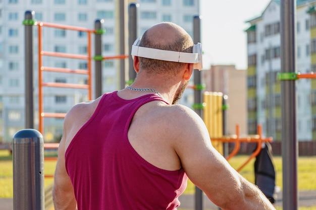 Gespierde man in koptelefoon luistert naar muziek op de speelplaats tijdens een sporttraining.