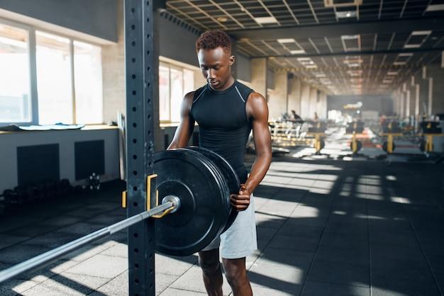 Gespierde man in sportkleding bereidt barbell voor op training in de sportschool. training in sportclub, gezonde levensstijl
