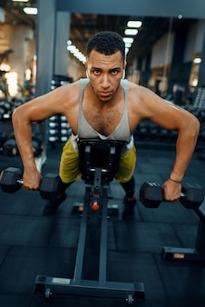 Gespierde man in sportkleding doen oefening met halters op de bank, training in de sportschool.