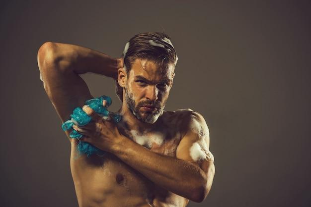 Gespierde man met baard poseren in de badkamer. gespierde sexy macho douchen na de training. knap gespierd mannelijk model met zeeplichaam. kopieer ruimte voor reclame.