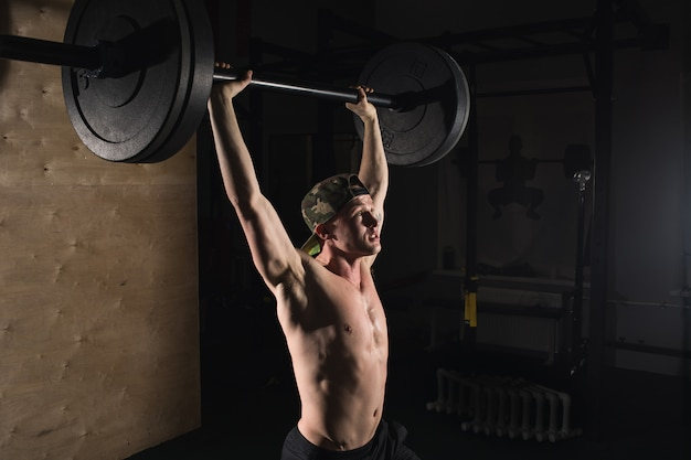 Gespierde man met baard trein met barbell verhoogd overhead in gym