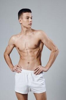 Gespierde man met een opgepompt lichaam die zijn handen aan zijn riem houdt, witte korte broek bijgesneden weergave