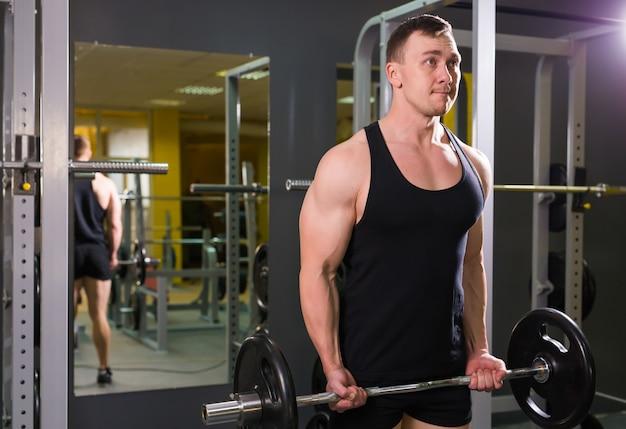 Gespierde man met het optrekken van halter in fitness training klasse binnenshuis