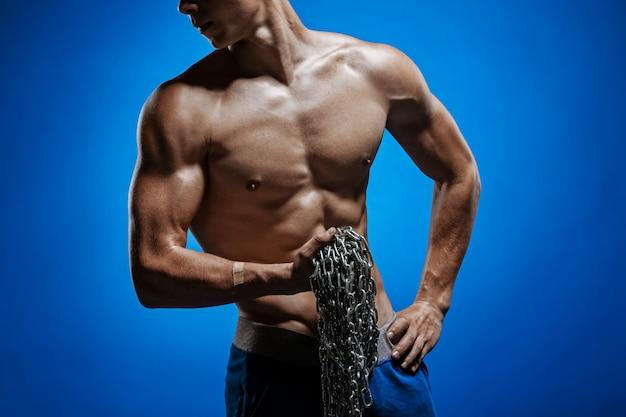 Gespierde man met kettingen op zijn schouders tegen een blauwe muur