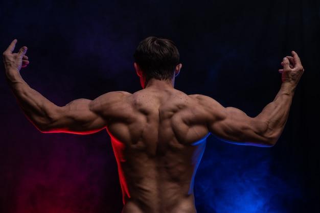 Gespierde man met spieren geïsoleerd op de zwarte achtergrond met gekleurde rook