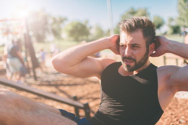 Gespierde man oefenen doen sit-up oefening. atleet met zes pack, blanke man, outdoor training. sport en een gezonde levensstijl. bebaarde zwartharige man doet crunches buitenshuis.