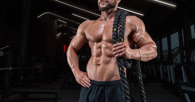 Gespierde man poseren in de sportschool met een touw. geschiktheidsconcept. gemengde media