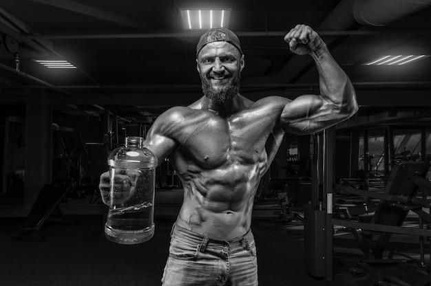 Gespierde man staat in de sportschool met een enorme fles sportvoeding. fitness en bodybuilding concept. gemengde media