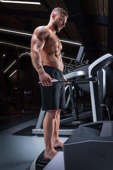 Gespierde man staat op een speciaal apparaat om de hoeveelheid lichaamsvet te analyseren. geschiktheidsconcept. gemengde media