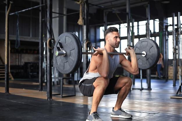 Gespierde man trainen in de sportschool doen oefeningen met barbell op biceps.