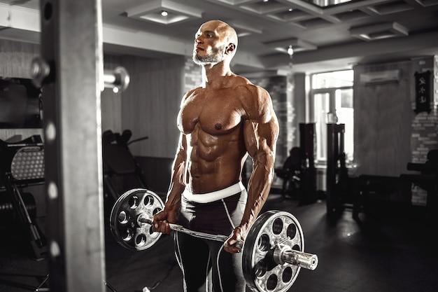 Gespierde man trainen in de sportschool doen oefeningen met halters