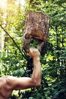 Gespierde man training met houten kettlebell in bos