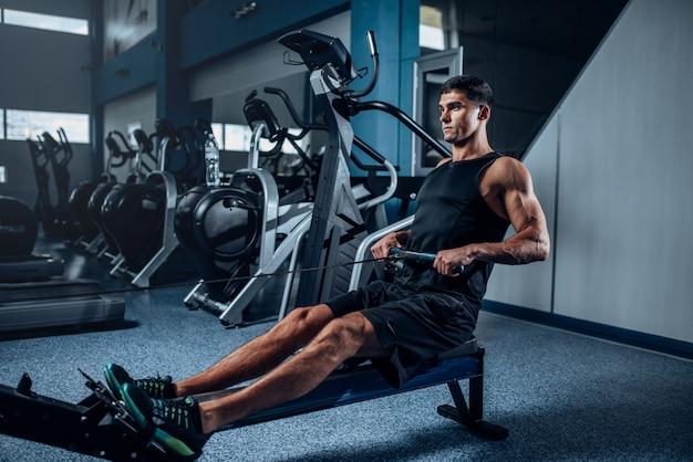 Gespierde man training op hometrainer. actieve sporttraining in de sportschool