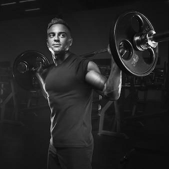 Gespierde man training squats met halters boven het hoofd