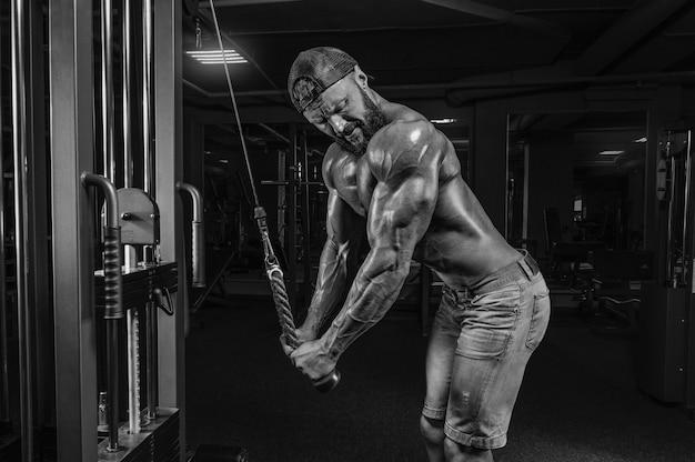 Gespierde man traint in de sportschool. triceps oefeningen. fitness en bodybuilding concept. gemengde media