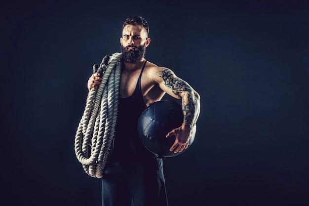 Gespierde man uit te werken met zwaar touw foto van man met naakte torso kracht en motivatie