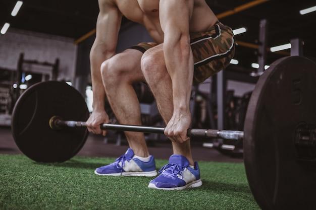 Gespierde mannelijke atleet uit te werken met barbell op gym studio