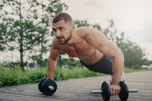 Gespierde mannelijke bodybuilder doet push-up met halters stands in plank pose met naakt lichaam