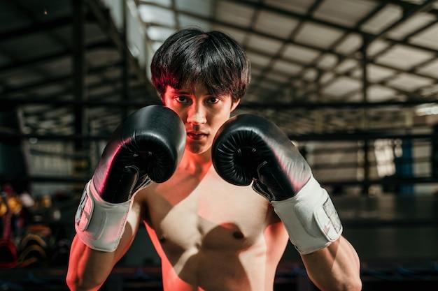 Gespierde mannelijke bokser bokshandschoenen dragen in de arena
