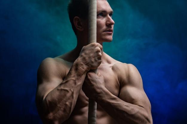 Gespierde mannelijke circusartiest met cord lisse op zwart een gerookte achtergrond