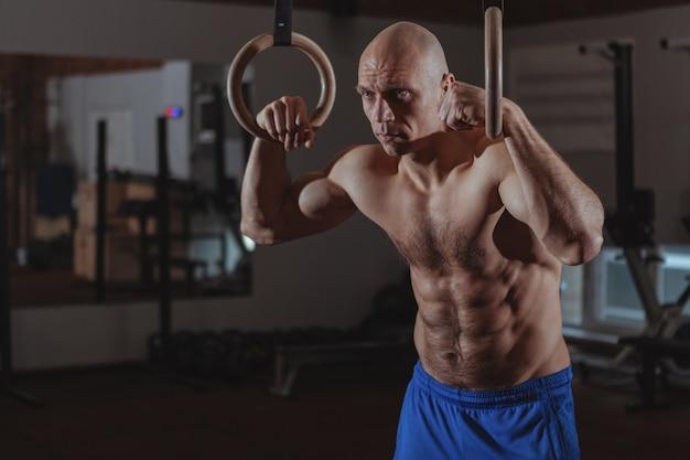 Gespierde mannelijke crossfit atleet trainen op gymnastiek ringen