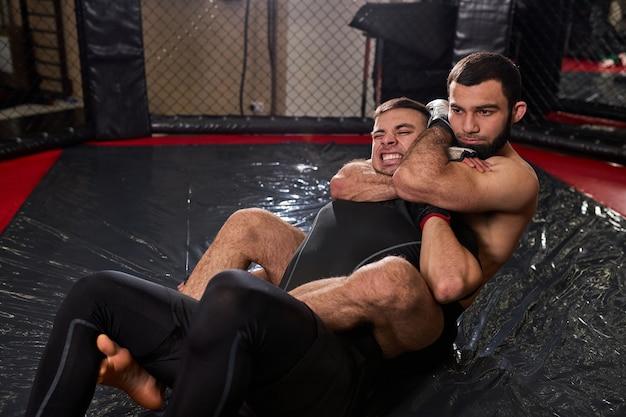 Gespierde mannen boksers in handschoenen vechten met behulp van grappling, zittend op de mat in de ring in de sportschool. kickboks- en sportconcept