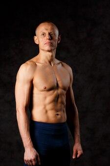 Gespierde model sport jonge man op donkere achtergrond. mode portret van sterke brute man met een moderne trendy kapsel. sexy romp. mannetje dat zijn spieren buigt. sport training bodybuilding concep.