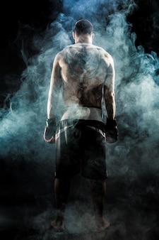 Gespierde muay thaise vechter met tatoeage die in rook achteruitgaat