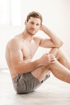 Gespierde perfectie. knappe jonge shirtloze man in korte broek zittend op de vloer