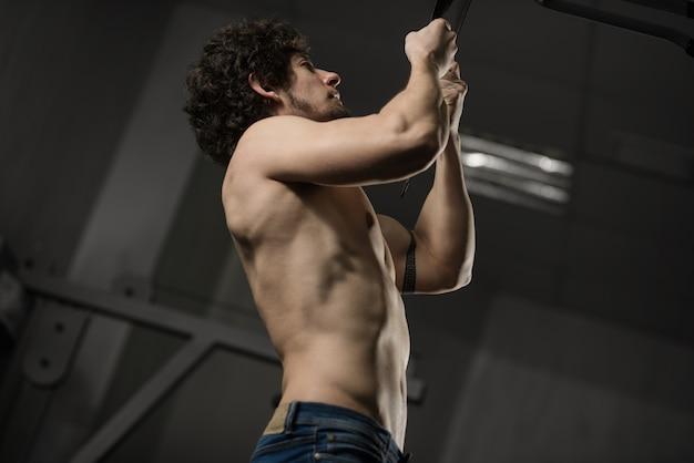 Gespierde persoon traint in de sportschool, voert oefening op handen uit, zijn naakte torso, spieren worden gespannen