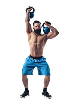 Gespierde shirtless getatoeëerde bebaarde mannelijke atleet bodybuilder training met kettlebell op een witte muur. isoleren