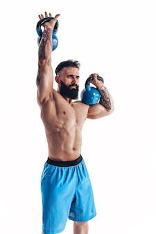Gespierde shirtless getatoeëerde bebaarde mannelijke atleet bodybuilder training met kettlebell