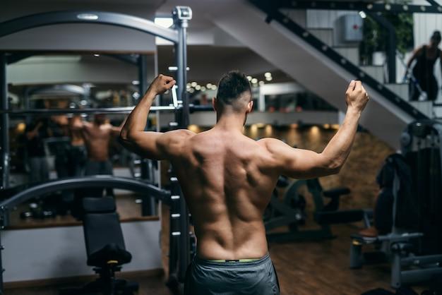Gespierde shirtless man poseren in de sportschool met opgeheven armen