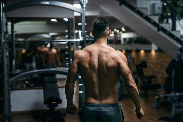Gespierde shirtless man poseren in de sportschool. rug draaide zich om.
