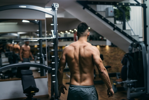 Gespierde shirtless man poseren in de sportschool