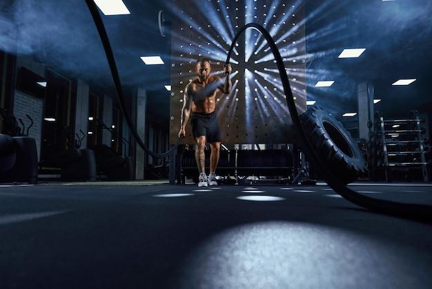 Gespierde shirtless sportman training met touwen.