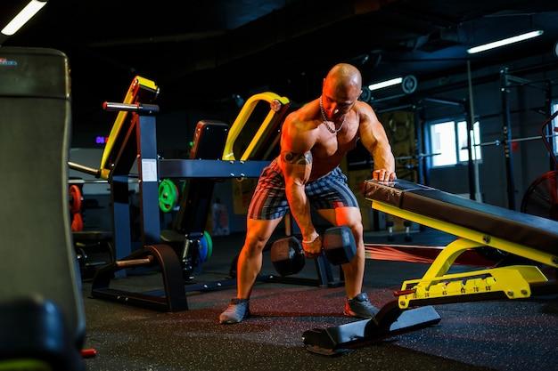 Gespierde shirtloze man die dumbbell-oefeningen doet als onderdeel van zijn bodybuilding-training. fitnessmotivatie, sportlevensstijl, gezondheid, atletisch lichaam, lichaamspositief
