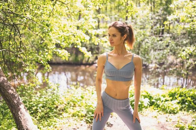 Gespierde slanke aantrekkelijke vrouw in sportkleding met platte buik en perfect fit lichaam in zomer park buiten