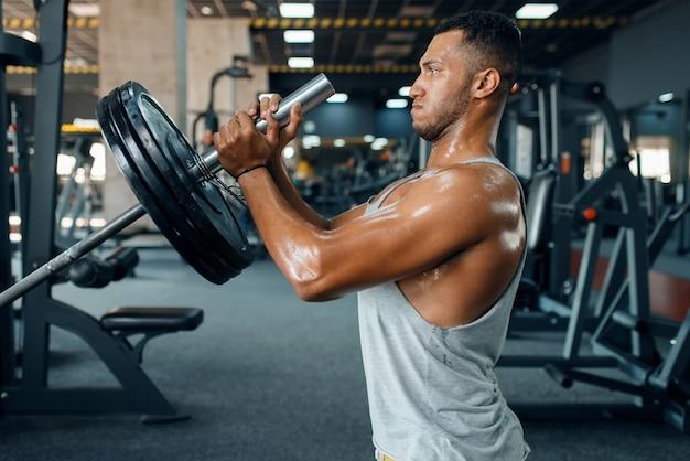 Gespierde sporsman in sportkleding oefening met barbell op training in de sportschool doet.