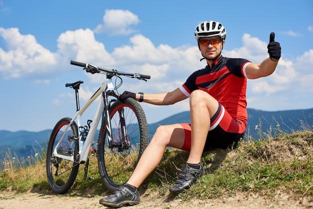 Gespierde sportman fietser zitten in de buurt van zijn mountainbike op met gras begroeide kant van de weg, duimen opdagen, rust na het rijden fiets op zonnige zomerdag. buitensport concept