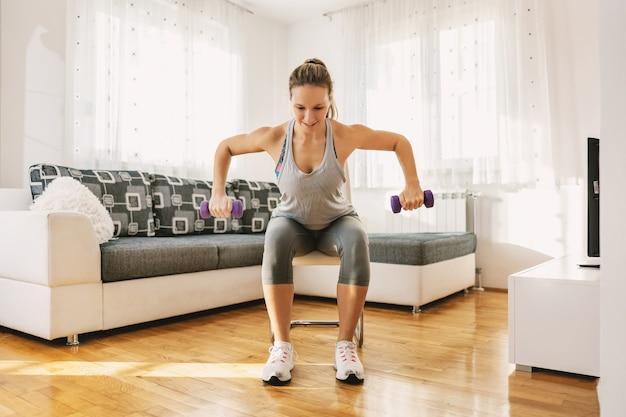 Gespierde sportvrouw in vorm zittend op de stoel thuis en halters op te heffen.