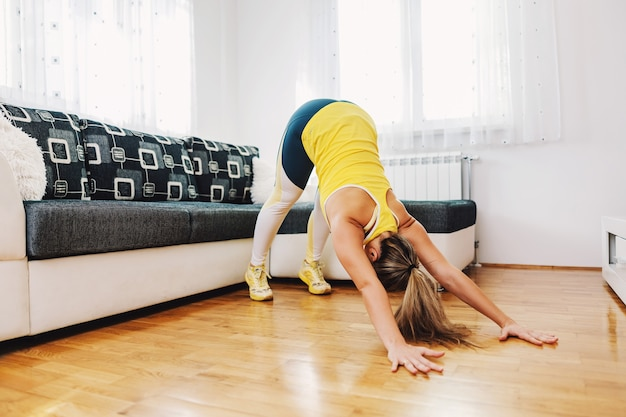 Gespierde sterke sportvrouw doet rekoefeningen op de vloer thuis