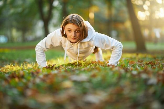Gespierde vrouw die buikspieren traint in stadspark