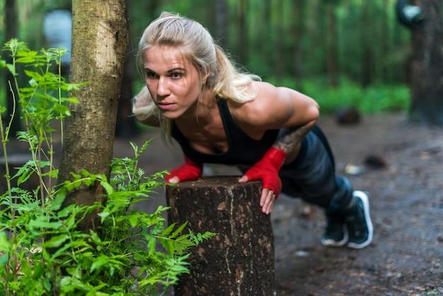 Gespierde vrouw doet push-ups in park street trainen