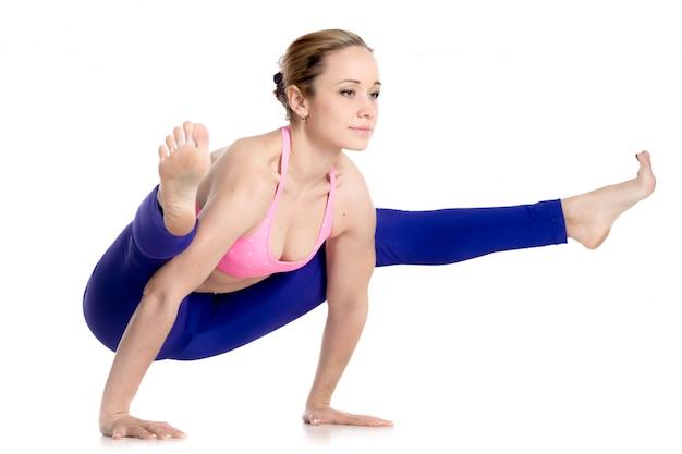 Gespierde vrouw met geavanceerde yoga pose