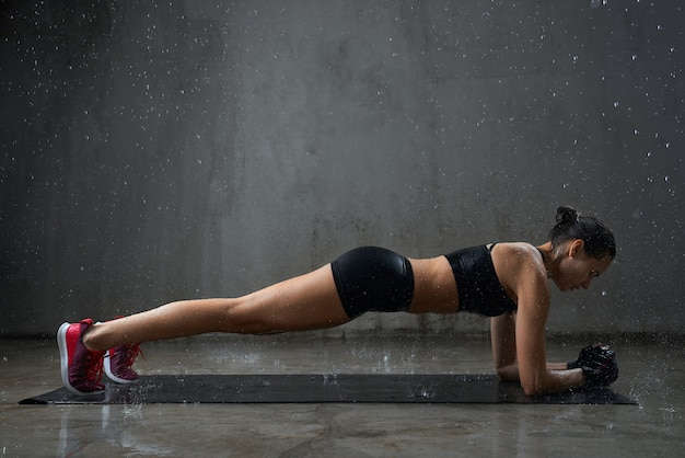 Gespierde vrouw plank oefening doet